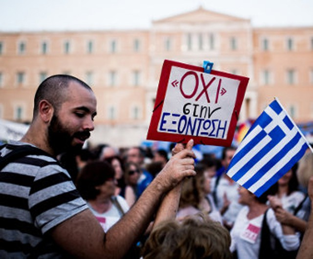 "A protestor outside the Greek parliament building on 29 June 2015, holding a sign reading ""no to annihilation"". Photo: Jan Wellmann/Wikimedia"